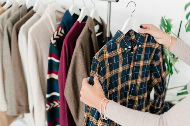 Young female shopper holding hanger with checkered shirt while choosing new casual clothes in boutique