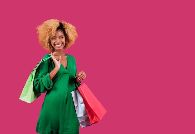 Молодая покупательница смотрит в камеру и улыбается, держа в руках красочные хозяйственные сумки на изолированном фоне. концепция продажи черная пятница.