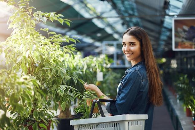 카메라 웃 고보고 녹지 저장소에 식물에 대 한 쇼핑하는 젊은 여성.