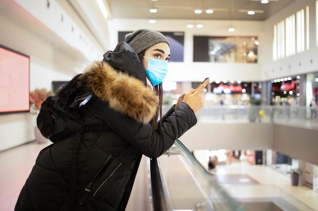 코로나 바이러스 전염병 동안 쇼핑몰에서 쇼핑하는 젊은 여성