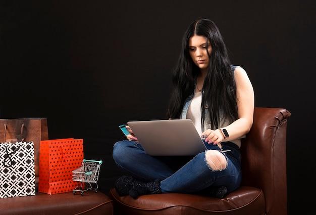 Молодая женщина, делающая покупки онлайн дома, сидя рядом с сумками, изолированными на темноте