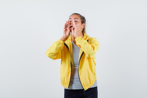 Молодая женщина кричит или объявляет что-то в куртке, футболке, вид спереди.