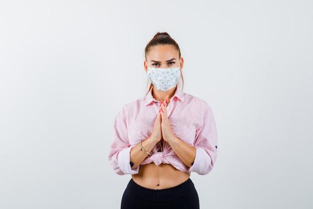 Молодая женщина показывает сложенные руки в умоляющем жесте в рубашке, штанах, медицинской маске и выглядит обнадеживающей. передний план.