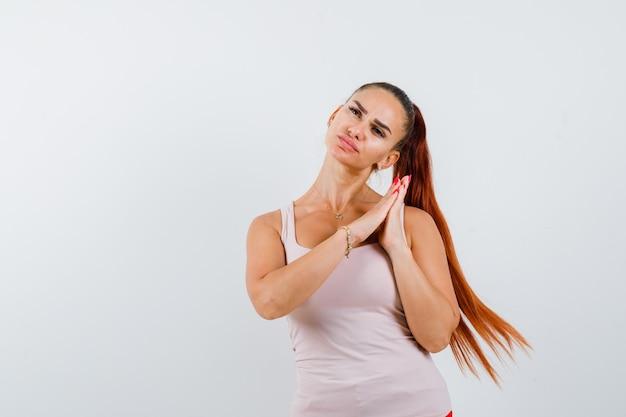 Молодая женщина показывает сложенные руки в умоляющем жесте в белой майке и выглядит мирно, вид спереди.