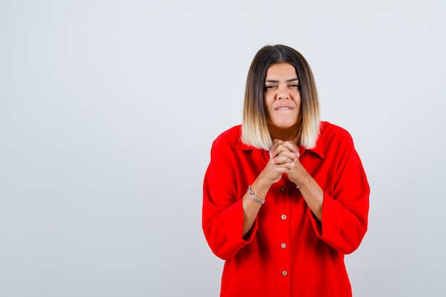 Young female showing clasped hands in pleading gesture in red oversized shirt and looking hopeful. front view.