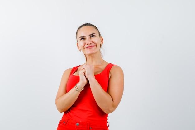 Giovane femmina che mostra le mani giunte nel gesto di supplica in canottiera rossa, pantaloni e sguardo pacifico. vista frontale.