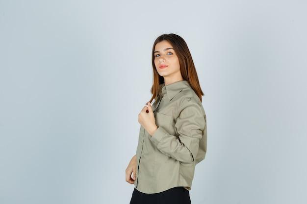 Giovane femmina che mostra pugno chiuso in camicia, gonna e guardando fiducioso, vista frontale.