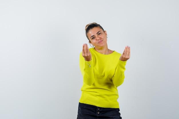 Giovane donna che mostra un gesto delizioso in maglione, gonna di jeans e sembra felice