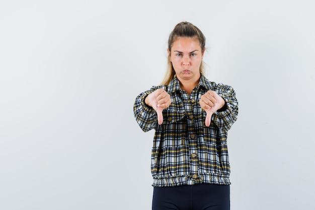 젊은 여성 셔츠, 반바지 아래로 두 엄지 손가락을 보여주는 우울한, 전면보기.