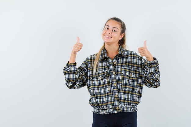 チェックのシャツを着て二重の親指を示し、陽気に見える若い女性、正面図。