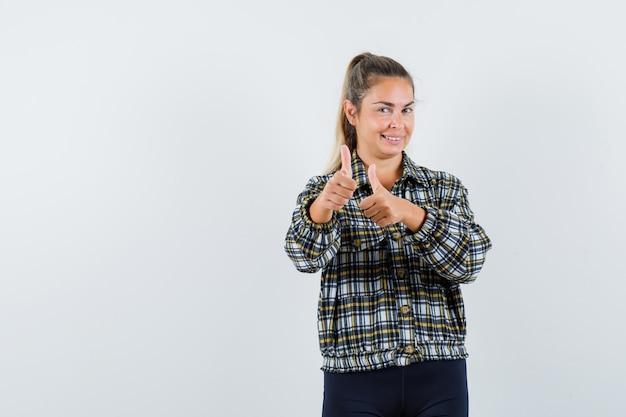 若い女性はシャツ、ショートパンツで二重の親指を示し、自信を持って見えます。正面図。