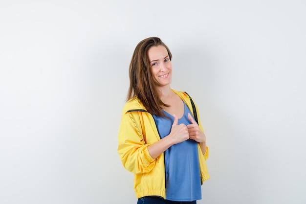 Giovane femmina che mostra doppio pollice in alto in t-shirt, giacca e sembra allegra. vista frontale.
