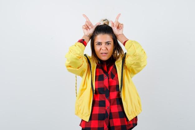 Молодая женщина показывает рога пальца над головой в клетчатой рубашке, куртке и выглядит весело. передний план.