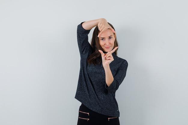 Молодая женщина показывает жест кадра в черной блузке и выглядит радостной