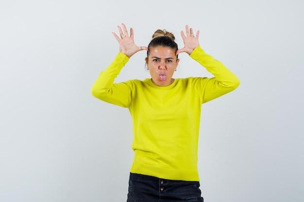 Giovane donna che mostra un gesto divertente in maglione, gonna di jeans e sembra carina