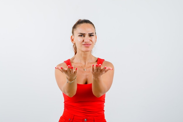 Young female showing giving gesture in red tank top, pants and looking cute , front view.