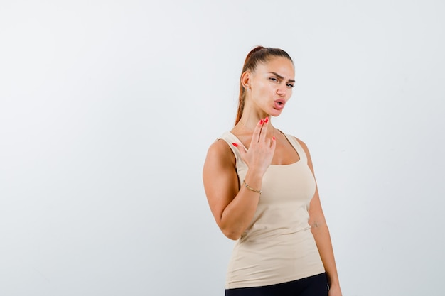 Young female showing gun gesture in beige tank top and looking confident. front view.