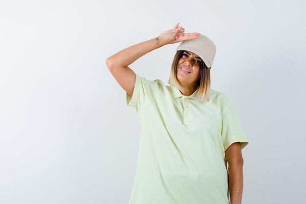 Tシャツ、キャップで頭上に銃のジェスチャーを示し、自信を持って見える若い女性。正面図。