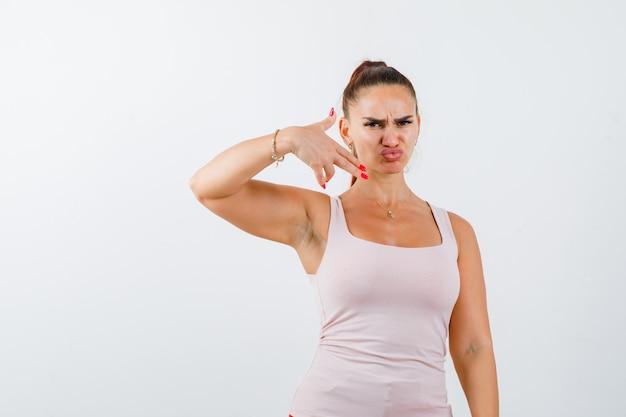 Giovane femmina che mostra il gesto della pistola in singoletto e guardando insoddisfatto, vista frontale.