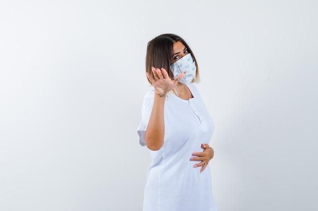 T- 셔츠, 마스크에 진정 하 고 자신감을 찾고 손을 보여주는 젊은 여성. 전면보기.