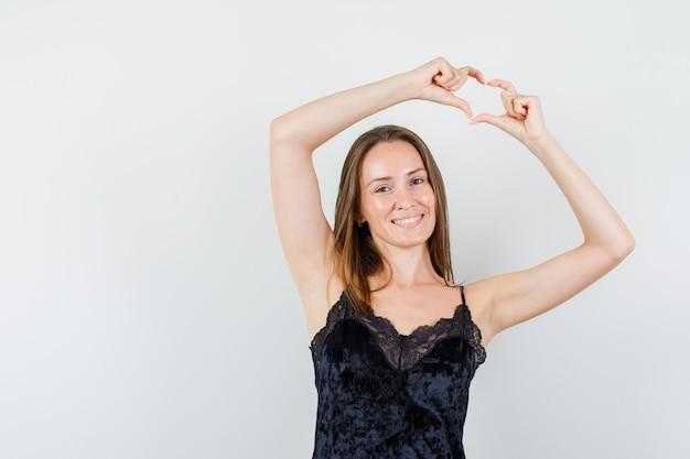 Молодая женщина показывает жест сердца в черной майке и выглядит радостной