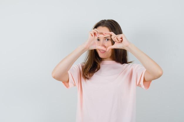 분홍색 티셔츠에 심장 제스처를 표시하고 귀여운, 전면보기를 찾고 젊은 여성.