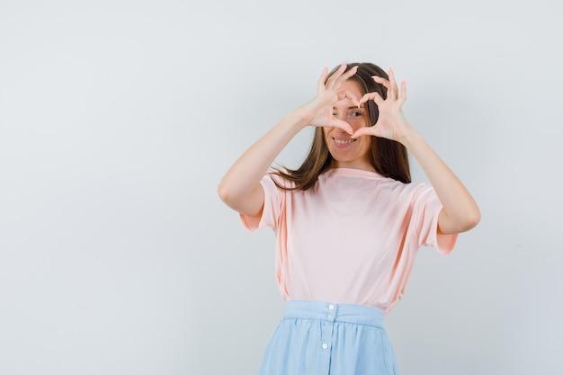 Молодая женщина показывает жест сердца в футболке, юбке и выглядит весело. передний план.