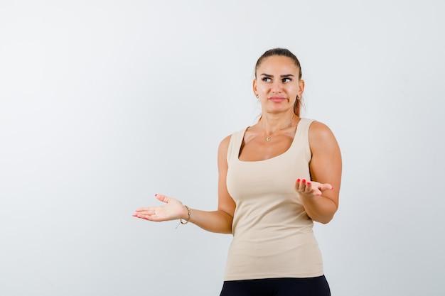 Giovane donna che mostra gesto impotente in canottiera beige e sembra all'oscuro. vista frontale.