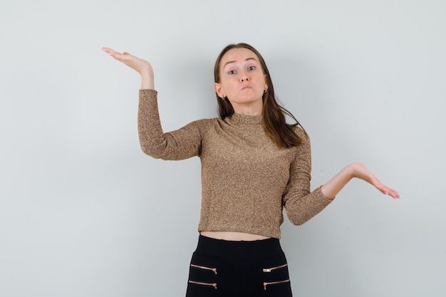 Young female showing helpless gesture in blouse,skirt and looking confused. front view.