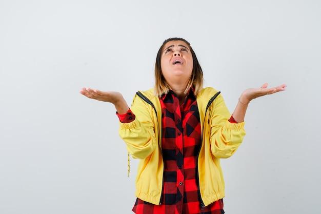市松模様のシャツ、ジャケットで無力なジェスチャーを示し、落ち込んでいる若い女性。正面図。