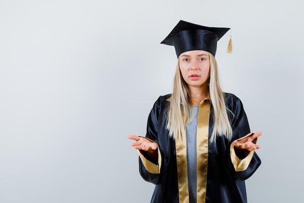 大学院の制服を着て無力なジェスチャーを示し、混乱しているように見える若い女性