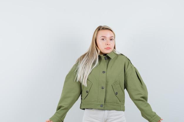녹색 재킷, 청바지에 무력한 제스처를 보여주는 젊은 여성 혼란, 전면보기를 찾고.