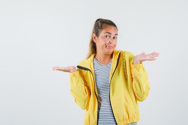 ジャケット、tシャツで無力なジェスチャーを示し、混乱しているように見える若い女性。正面図。