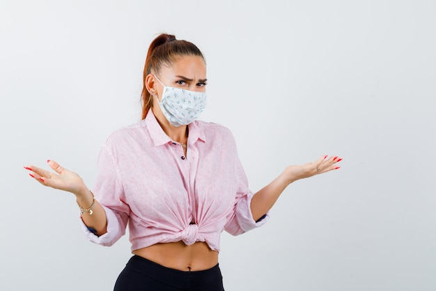 Молодая женщина показывает беспомощный жест в рубашке, штанах, медицинской маске и выглядит нерешительно. передний план.