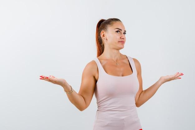 一重項で無力なジェスチャーを示し、躊躇している若い女性。正面図。
