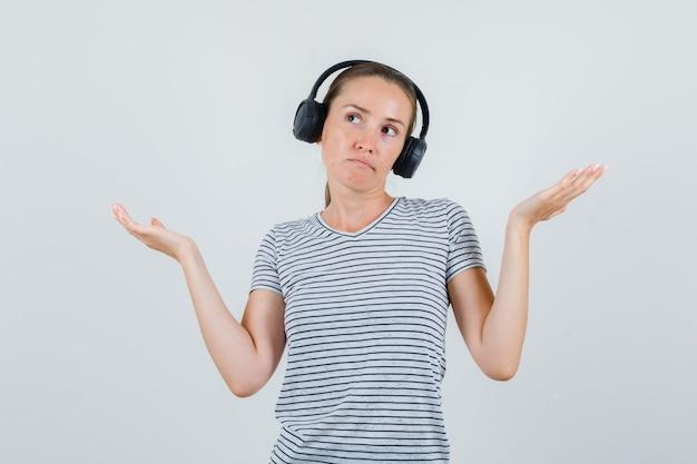 Молодая женщина показывает беспомощный жест в полосатой футболке, наушниках, вид спереди.