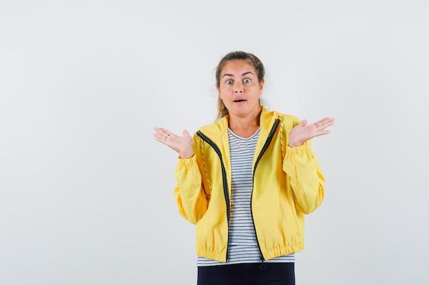 Giovane femmina che mostra gesto impotente in giacca, t-shirt e sembra confuso. vista frontale.