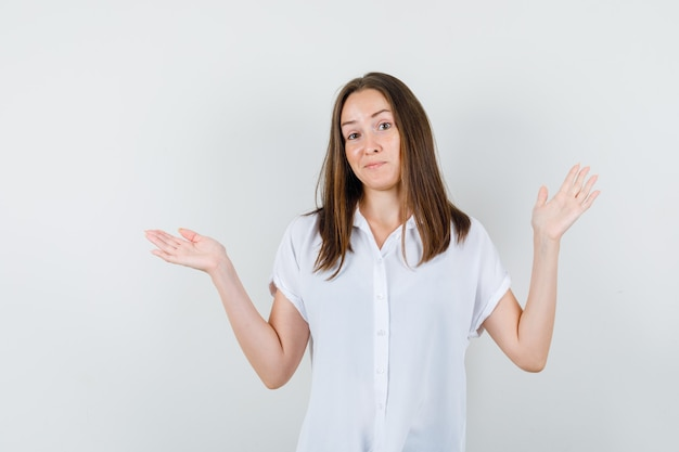 Young female showing helpless gesture in white blouse and looking puzzled
