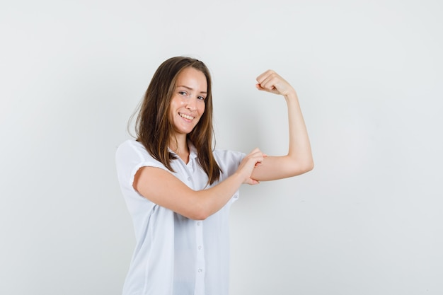 Young female showing her arm muscles in white blouse and looking powerful