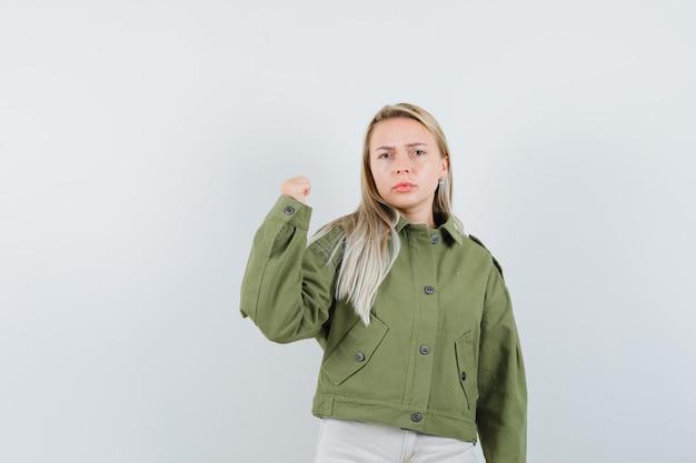 Giovane donna che mostra la sua potenza del braccio in giacca verde, jeans e che sembra seria, vista frontale.