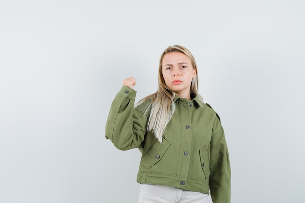 緑のジャケット、ジーンズで彼女の腕の力を示し、真剣に見える若い女性、正面図。
