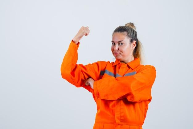 Giovane donna che mostra la sua potenza del braccio in uniforme da lavoro e che sembra sicura. vista frontale.