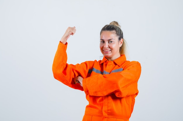 Giovane donna che mostra la sua potenza del braccio in uniforme da lavoro e sembra pronta. vista frontale. Foto Gratuite