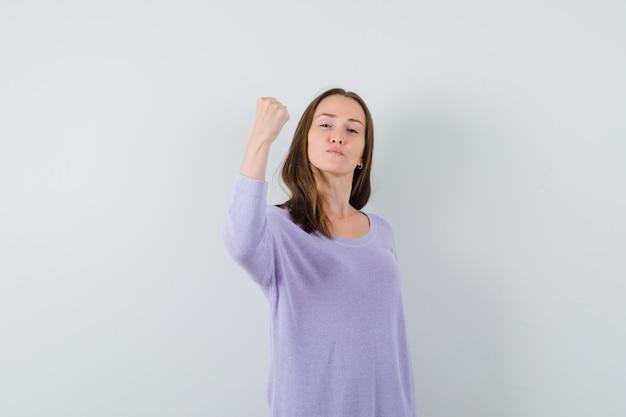 Giovane donna che mostra il suo potere in camicetta lilla e sembra sicura