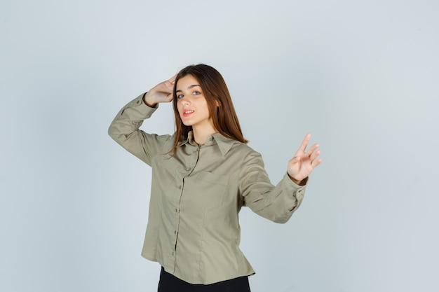 Giovane donna che mostra tenere un gesto minuto mentre tiene la mano sulla testa in camicia, gonna e sembra sicura, vista frontale.