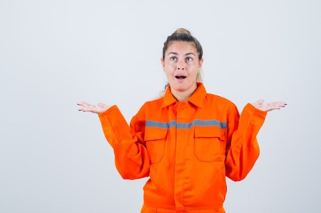Молодая женщина показывает жест idk в рабочей форме и выглядит смущенным. передний план.