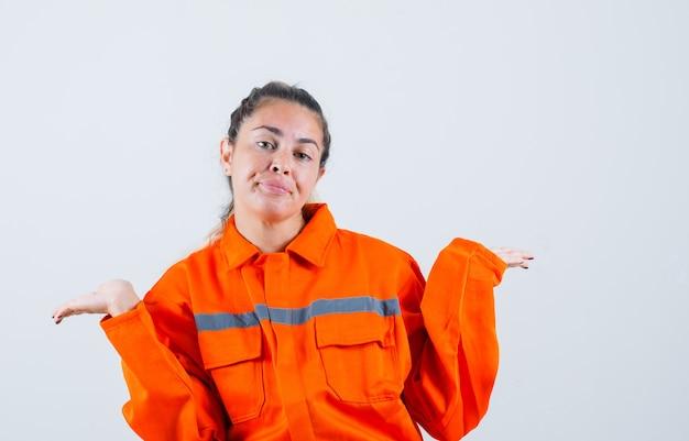 Молодая женщина показывает жест idk в форме работника, вид спереди.