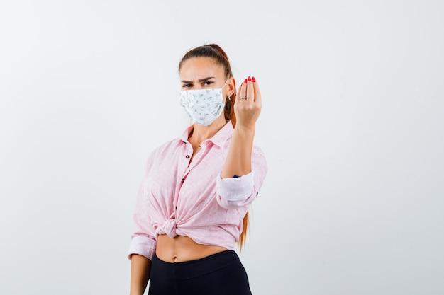 Giovane femmina che mostra gesto italiano in camicia, pantaloni, mascherina medica e sguardo felice. vista frontale.