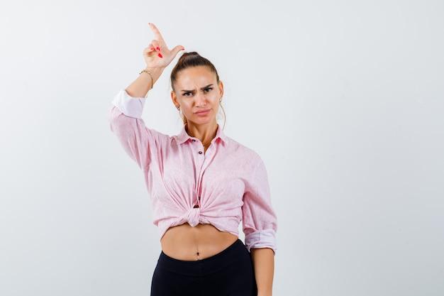 Молодая женщина показывает жест неудачника в повседневной рубашке и смотрит задумчиво, вид спереди.