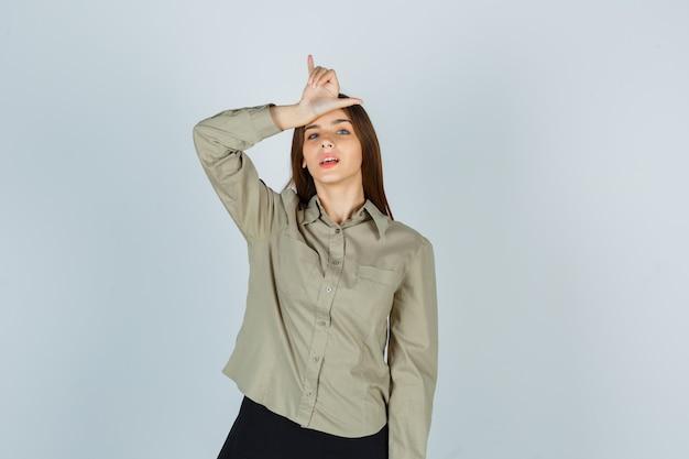 Giovane donna che mostra il segno del perdente sulla fronte in camicia, gonna e sembra sicura. vista frontale.